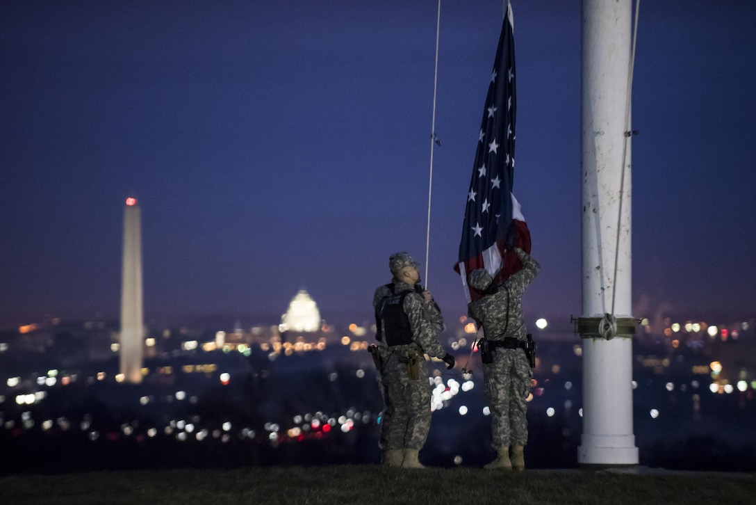 Pvt. Kaloni Alston (right), U.S. Army Reserve military police Soldier from Temple Hills, Md., with the 443rd MP Company, of the 200th MP Command, helps raise the American flag during a morning detail along with two active duty Soldiers from the 289th MP Co., belonging to the 3rd U.S. Infantry Regiment (The Old Guard), during a working partnership in the Military District of Washington, D.C., Feb. 17. This partnership pilot program began in early February, placing Army Reserve Soldiers on active duty orders for three weeks while working at Joint Base Myer-Henderson Hall, Fort Lesley J. McNair and the Arlington National Cemetery. Soldiers will also support the Military District of Washington with additional duty days throughout the year. (U.S. Army photo by Master Sgt. Michel Sauret)