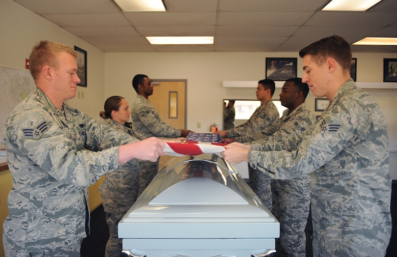 U.S. Airmen from the base honor guard practice a six-man flag folding sequence at Daivs-Monthan Air Force Base, Ariz., Feb 18, 2015. The honor guard's mission is to provide military funeral honors for members of the Air Force and its predecessors. D-M honor guardsmen train seven to eight hours a day to sharpen the sequences they perform during details. (U.S. Air Force photo by Senior Airman Cheyenne A. Powers/ Released)