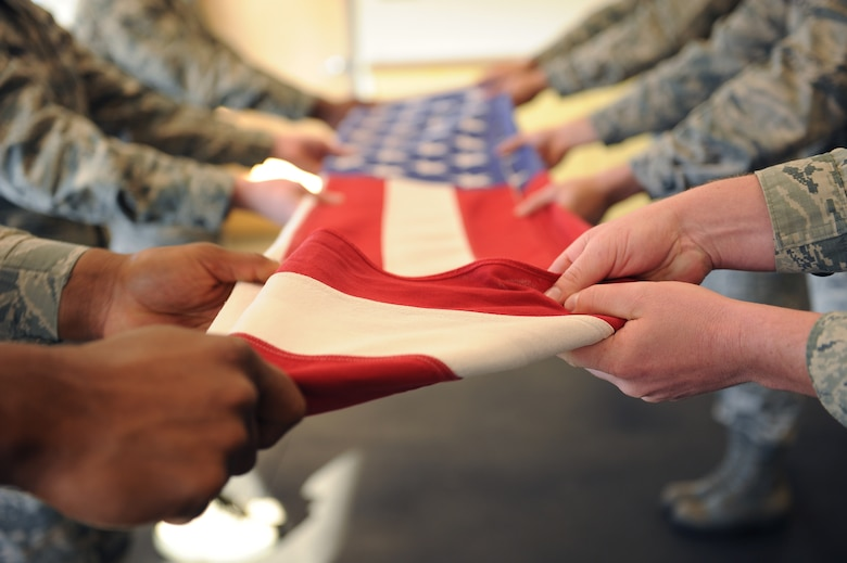 U.S. Airmen from the base honor guard practice folding an American flag at Davis-Monthan Air Force Base, Ariz., Feb 18, 2016. The team practices seven to eight hours a day to perfect their skills. (U.S. Air Force photo by Senior Airman Cheyenne A. Powers/ Released)