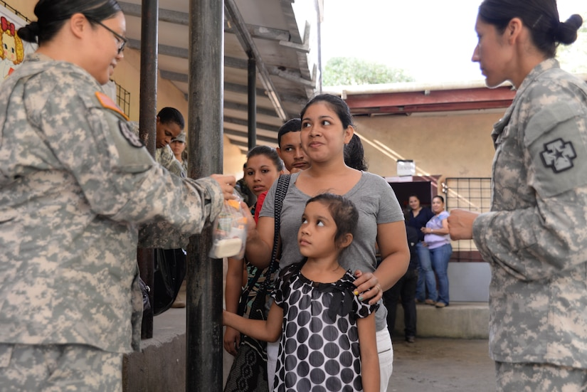 U.S. Army Sgt. Mary King, preventative medicine technician, gives a woman a bag of preventative supplies during a medical readiness training exercise in the Cortes Department, Honduras, Feb. 18, 2016. Preventative medicine aims to stop sickness before it spreads by providing vitamins, soap, and other essential items.  (U.S. Air Force Photo by Staff Sgt. Westin Warburton/Released)
