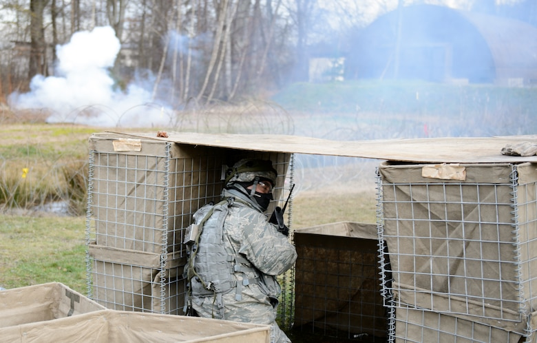 A 1st Combat Communications Squadron Airman calls back as instructors release mock mortars on the compound Feb. 12, 2016, at Ramstein Air Base, Germany. The 1st CBCS conducts regular deployment skills training to prepare Airmen for any situation they may encounter. (U.S. Air Force photo/Staff Sgt. Armando A. Schwier-Morales)