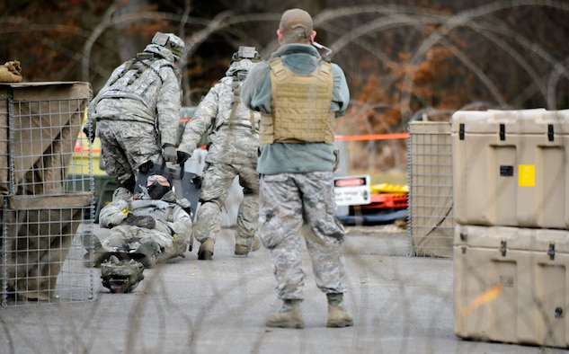 """A 1st Combat Communications Squadron instructor watches as trainees drag a """"wounded"""" Airman away to a mock field hospital Feb. 12, 2016, at Ramstein Air Base, Germany. The Airmen are training to maintain deployment skills to ensure be able to defend their multi-million dollars of assets. (U.S. Air Force photo/Staff Sgt. Armando A. Schwier-Morales)"""