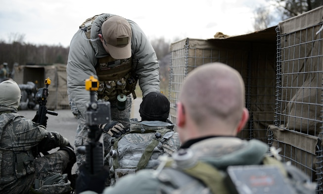 """Staff Sg. John Burchfield, 1st Combat Communications Squadron instructor, """"revives"""" Airmen who have been hit during the mock fire-fight at Ramstein Air Base, Germany, Feb. 12, 2016. The 1st CBCS uses lasers to determine when an Airman has been hit by opposing forces in order to make the training more realistic. (U.S. Air Force photo/Staff Sgt. Armando A. Schwier-Morales)"""