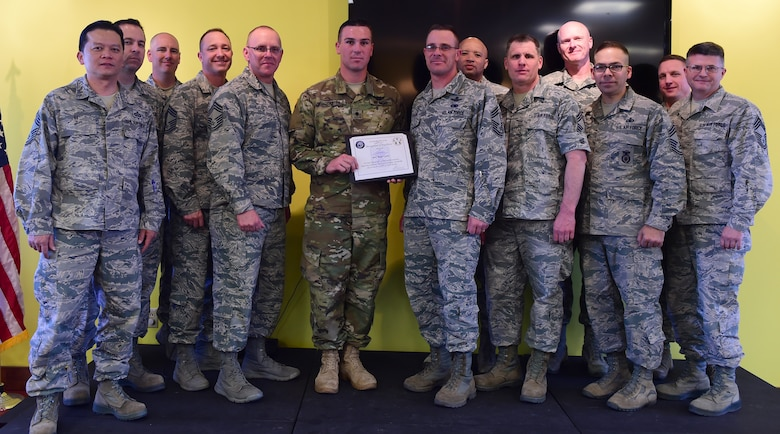 U.S. Army Spc. Brian Carter, 743d Military Intelligence Battalion analyst, stands with the Team Buckley Chief's Group at the Panther Den Feb. 18, 2016, on Buckley Air Force Base, Colo. Carter exemplified excellence by taking on multiple leadership positions and providing fidelity on global weapon capability, which protected the nation's warfighters in three areas of responsibilities. (U.S. Air Force photo by Senior Airman Racheal E. Watson/Released)