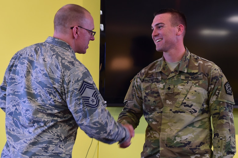 U.S. Air Force Chief Master Sgt. Richard Halseth, Team Buckley Chief's Group member, shakes hands with U.S. Army Spc. Brian Carter, 743d Military Intelligence Battalion analyst, at the Panther Den Feb. 18, 2016, on Buckley Air Force Base, Colo. Carter was recognized by the Team Buckley Chief's Group for going above and beyond the call of duty. (U.S. Air Force photo by Senior Airman Racheal E. Watson/Released)