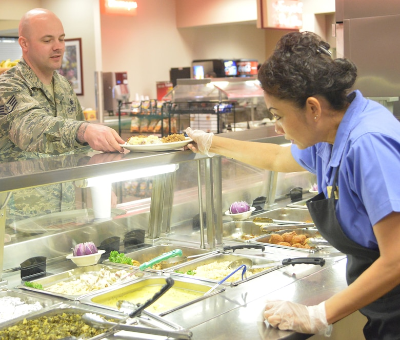 Sompit Amonchomchupong, Wynn Dinning Facility line server and cashier, dishes up lunch for Staff Sgt. Philip Arras with the 78th Security Forces Squadron. (U.S. Air Force photo by Ray Crayton)
