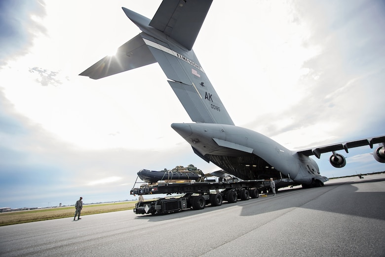 A team from the 920th Rescue Wing loads a Rigging Alternate Method Zodiac package onto a C-17 Globemaster III aircraft from the 249th Airlift Squadron, Alaska Air National Guard, at Patrick Air Force Base, Fla., Jan. 14 after packaging the equipment for an airdrop during a simulated astronaut recovery mission. The 249th AS worked with NASA, the 920th Rescue Wing, the 45th Space Wing and Detachment 3 of the 45th Operations Group to develop tactics, training and procedures to quickly and safely recover astronauts in the event they would need to abort their spacecraft. (Courtesy photo by Senior Airman Zac Heinen)