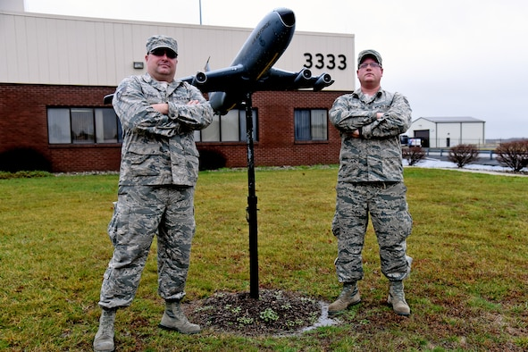 Staff Sgts. Murray Burgen, left, and Shaun Strain, both with the 108th Maintenance Group, pose in front of a KC-135E Stratotanker model in front of hangar 33-33. The aircraft structural maintenance craftmen worked on updating and remodeling the fiber-glassed display. (U.S. Air National Guard photo by Tech. Sgt. Armando Vasquez/Released)