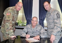 "From left: Army Col. Mark A. Lee, 502nd Air Base Wing and Joint Base San Antonio vice commander; Brig. Gen. Bob LaBrutta, 502nd ABW and JBSA commander; and Command Chief Master Sgt. Stanley C. Cadell, 502nd ABW and JBSA Command Chief, sign the Military Saves Pledge to ""Set A Goal. Make a Plan. Save Automatically."" Military Saves Week begins Monday and runs through Feb. 26 throughout JBSA. The pledge is a commitment to exercise good financial habits, improve financial readiness and encourage other Americans to do the same."
