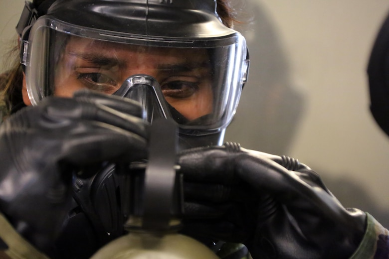 A Marine attaches a canteen to her M50 Joint Service General Purpose Mask during gas chamber training at Marine Corps Air Station Cherry Point, N.C., Feb. 10, 2016. Marines with Marine Aviation Logistics Squadron 14 faced the CS gas as part of their qualification to familiarize themselves with the equipment and skills if faced with a biochemical attack. Marines of every military occupational specialty must be proficient with the equipment as it is part of every Marines' basic skills. (U.S. Marine Corps photo by Cpl. N.W. Huertas/Released)