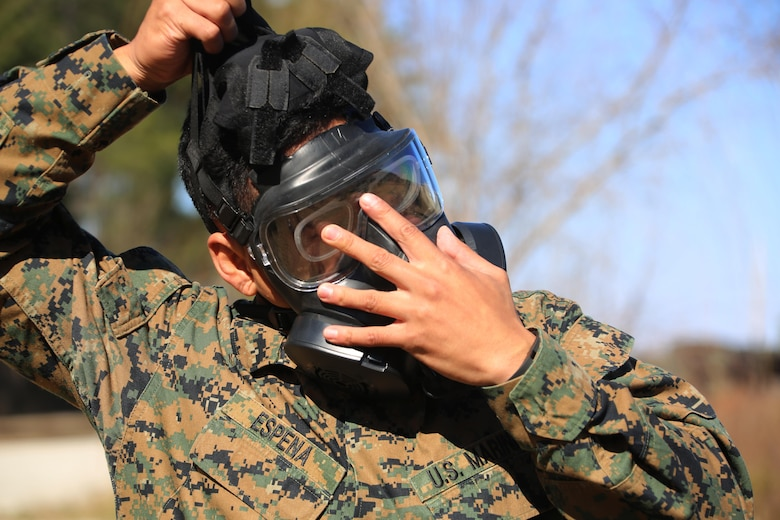 Cpl. Justin D. Espena removes his M50 Joint Service General Purpose Gas Mask after exciting the gas chamber at Marine Corps Air Station Cherry Point, N.C., Feb. 10, 2016. Marines with Marine Aviation Logistics Squadron 14 faced CS gas in the gas chamber as part of their qualification to familiarize themselves with the equipment and skills if faced with a biochemical attack. Marines of every military occupational specialty must be proficient with the equipment as it is part of every Marines' basic skills. Espena is an aircraft maintenance  support equip hydraulic, pneumatic, structure mechanic with MALS-14. (U.S. Marine Corps photo by Cpl. N.W. Huertas/Released)