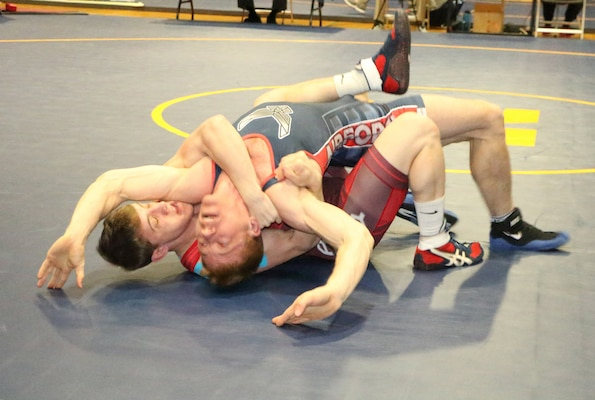 Army Pfc. Michael Hooker (red) wraps up Air Force Capt. Kurt Spranger of Wright-Patterson AFB, Ohio to win Armed Forces gold in the 65kg Freestyle competition of the 2016 Armed Forces Wrestling Championship held at Naval Base Kitsap, Wash. 20-21 February 2016.