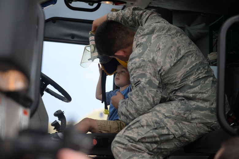 Airman 1st Class Jared May, 36th Civil Engineer Squadron firefighter, helps place a fire helmet on a child's head Feb. 20 during the 2016 Pacific Air Partners Open House at Andersen Air Force Base, Guam. May, alongside other members of the fire department, provided attendees the opportunity to sit in a fire truck and learn about their mission. (U.S. Air Force photo/Senior Airman Joshua Smoot)