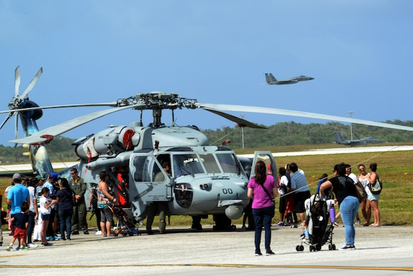 A F-15 Eagle soars past a crowd of people admiring a Helo Feb. 20 during the 2016 Pacific Air Partners Open House at Andersen Air Force Base, Guam. The open house aims to enhance public awareness of the military's mission, equipment, facilities and personnel and to promote positive community relations. (U.S. Air Force Photo/Airman 1st Class Alexa Ann Henderson)