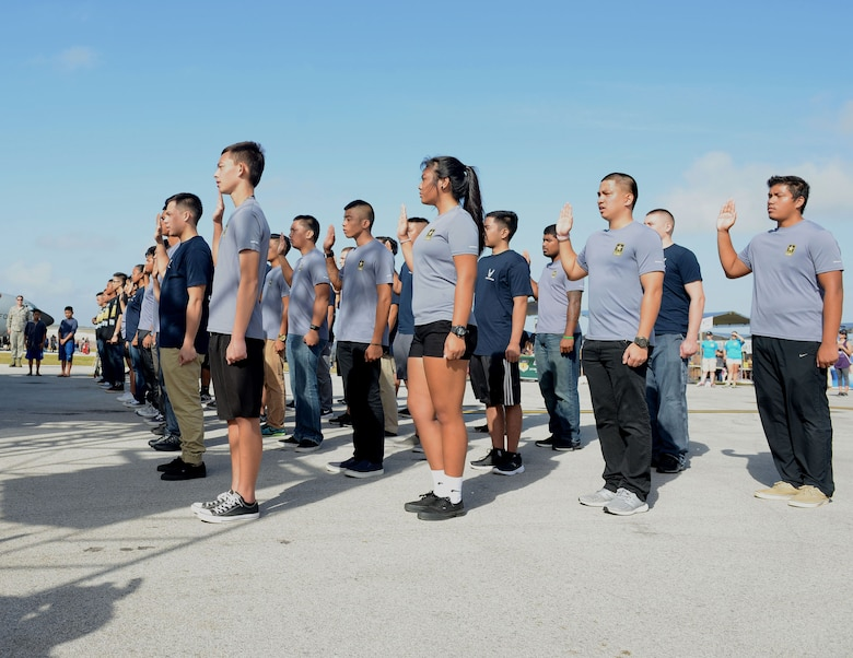 U.S. Air Force and Army recruits raise their right hand at an enlistment ceremony Feb. 20 during the 2016 Pacific Air Partners Open House at Andersen Air Force Base, Guam. Brig. Gen. Andrew Toth, 36th Wing commander, swore in more than 30 recruits into the U.S. Air Force, Army and Air National Guard. (U.S. Air Force photo/Airman 1st Class Arielle Vasquez)