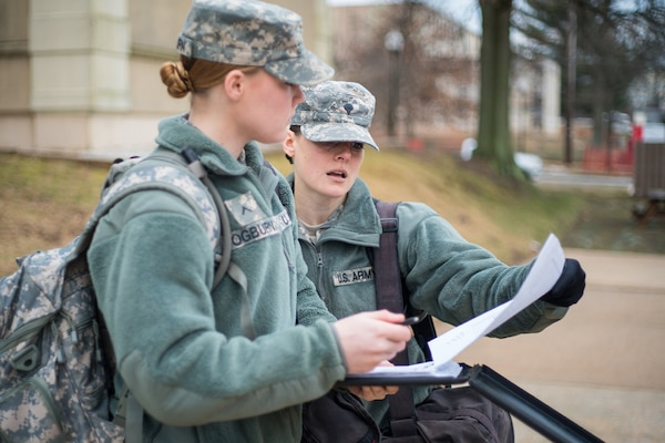 Army Spc. Amy Carle, a student at the Defense Information School on Fort Meade, Md., and a platoon guide at the U.S. Army Signal School Detachment Student Company on post, helps a fellow soldier, Pfc. Lauren Ogburn, on Feb. 17, 2016, before a morning formation. Carle, who works for Google at the company's headquarters in Mountain View, California, joined the California National Guard in 2014 with a desire to use her professional skills to serve the country.