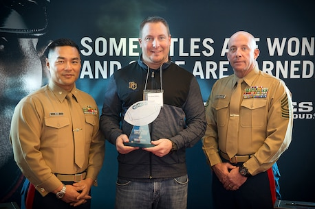 Jeremy Thielbahr, the head football coach for Eastside Catholic School in Sammamish, Wash., received the Semper Fi Coach Award from Maj. Sung Kim and Sgt. Maj. Jeffrey Dagenhart, the commanding officer and senior enlisted advisor of Marine Corps Recruiting Station Seattle, during a Glazier Clinics event in Seattle, Feb. 20, 2016. Thielbahr, ECS' head football coach, was recognized for embodying the Marine Corps' core values of honor, courage and commitment. Last December, he led his team to overcome a 28-point deficit and beat Bellevue High School 48-42 in overtime, clinching the Class 3A state championship. (U.S. Marine Corps photo by Sgt. Reece Lodder)