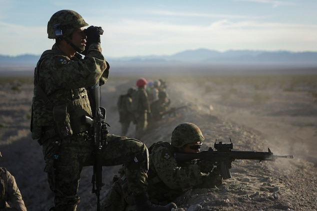 A rifleman assigned to Western Army Infantry Regiment, Japan Ground Self Defense Force, observes the impact area as several service members fire on simulated targets, during a live-fire platoon level assault, during Exercise Iron Fist 2016 aboard Marine Corps Air Ground Combat Center Twentynine Palms, Feb. 9, 2016. Iron Fist is an annual, bi-lateral training exercise between the Japan Ground Self Defense Force and Marines to strengthen warfighting capabilities in ship to shore operations.