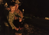 Team Vance kid Rex Layne plays fireman with the pros as he pairs with Firefighter Josh Stephens at Vance Air Force Base, Oklahoma, Jan. 29. Vance Fire Department firefighters helped close the night's Mardi Gras celebration by monitoring a celebratory bonfire. ( U.S. Air Force photo / David Poe)