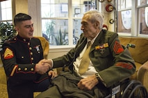 Sgt. Luis Urquijo, an administration/personnel specialist with Recruiting Station Denver, shakes hands with Ken Bradford, a World War II Marine veteran, at the Sunrise at Orchard Senior Living Home in Littleton, CO, Feb. 21, 2016. Bradford served on Iwo Jima, Hawaii and Guam during his enlisted career.