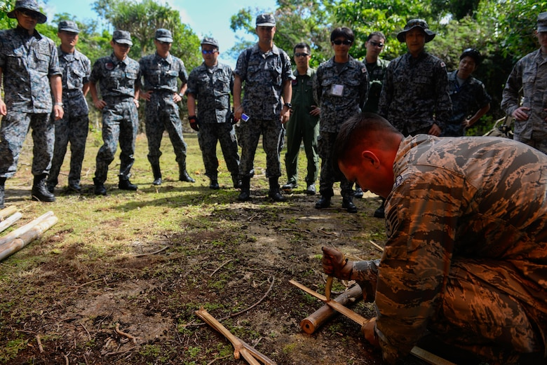 Staff Sgt. Levi Wood, survival, evasion, resistance and escape instructor assigned to the 353rd Combat Training Squadron, shows visiting Japan Air Self-Defense Force airmen how to safely split bamboo to start a fire Feb. 16, 2016, at Andersen Air Force Base, Guam. Exercise Cope North 16 includes 22 total flying units and nearly 3,000 personnel from six countries and continues the growth of strong, interoperable and beneficial relationships within the Indo-Asia-Pacific Region through integration of airborne and land-based command and control assets. (U.S. Air Force photo by Staff Sgt. Alexander W. Riedel/Released)