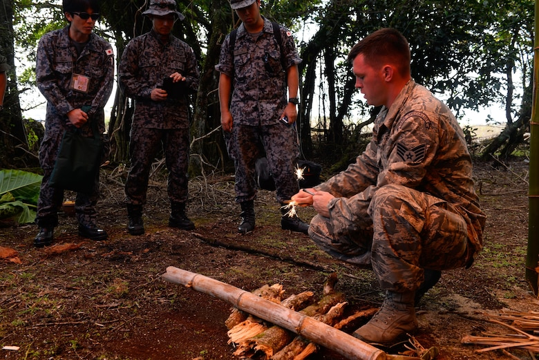 Staff Sgt. Levi Wood, a survival, evasion, resistance and escape instructor assigned to the 353rd Combat Training Squadron, shows visiting Japan Air Self-Defense Force airmen how to safely start a fire using fire steel Feb. 16, 2016, at Andersen Air Force Base, Guam. Exercise Cope North 16 includes 22 total flying units and nearly 3,000 personnel from six countries and continues the growth of strong, interoperable and beneficial relationships within the Indo-Asia-Pacific Region through integration of airborne and land-based command and control assets. (U.S. Air Force photo by Staff Sgt. Alexander W. Riedel/Released)
