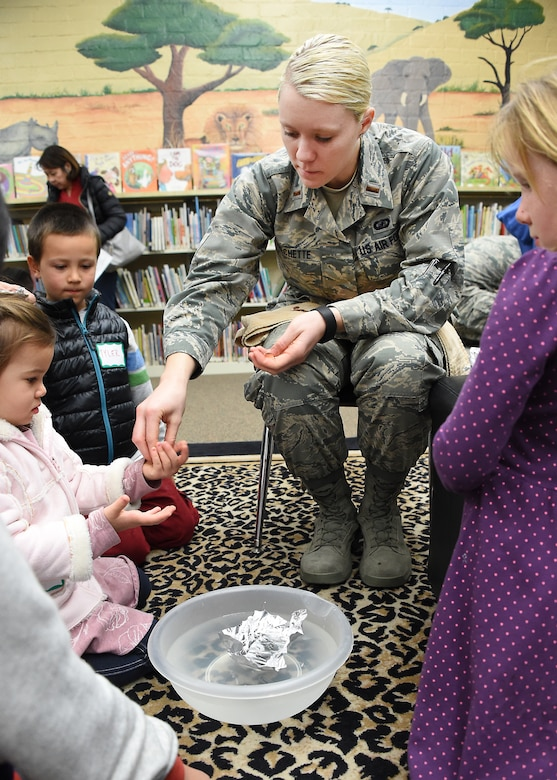 "U.S. Air Force 2nd Lt. Megan Frechette hands out pennies in the ""Aluminum Foil Boats"" demonstration, where students fashioned a boat out of foil and inserted pennies to see who could float the most pennies while learning about design and displacement. Thirty-seven volunteers from Los Angeles Air Force Base, El Segundo, Calif., visited Center Elementary School in El Segundo to staff various STEM (Science Technology Engineering Mathematics) experiment stations led by the Space and Missile Systems Center volunteers, where they work with the students at the Engineering/Building Stations and Food Science Experiment Stations to collect and discuss observed results, Feb 3, 2015 (U. S. Air Force photo Joseph M. Juarez Sr)"