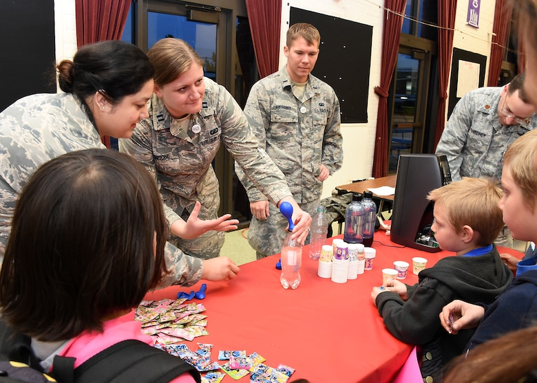 U.S. Air Force Tech. Sgt. Francis Osorio, (left to right) Capt. Rachel Simone, 1st Lt. Kyle Hathaway and Maj. Michael Schreiner operate the Food Science table to experiment with pressurized carbon dioxide, demonstrated by filling the balloon. Thirty-seven volunteers from Los Angeles Air Force Base, El Segundo, Calif., visited Center Elementary School in El Segundo to staff various STEM (Science Technology Engineering Mathematics) experiment stations led by the Space and Missile Systems Center volunteers, where they work with the students at the Engineering/Building Stations and Food Science Experiment Stations to collect and discuss observed results, Feb 3, 2015 (U. S. Air Force photo Joseph M. Juarez Sr)
