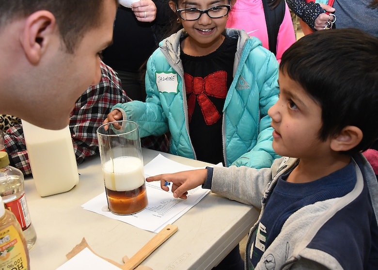 U.S. Air Force 1st Lt. Rinaldo Izzo pours milk and various other liquids to demonstrate and discuss the definition and relationship of density (mass/volume) with grade school students. Thirty-seven volunteers from Los Angeles Air Force Base, El Segundo, Calif., visited Center Elementary School in El Segundo to staff various STEM (Science Technology Engineering Mathematics) experiment stations led by the Space and Missile Systems Center volunteers, where they work with the student at the Engineering/Building Stations and Food Science Experiment Stations to collect and discuss observed results, Feb 3, 2015 (U. S. Air Force photo Joseph M. Juarez Sr)