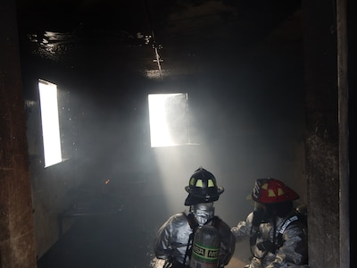 SOTO CANO AIR BASE, Honduras –Firefighters with, the 612th Air Base Squadron, finish putting out a fire in a burn house during a familiarization and proficiency exercise, Feb. 18, 2016, at Soto Cano Air Base, Honduras. These exercises test skills needed to respond to various scenarios, including structural fires like this one, and occur on a regular basis, honing  firefighters' skills to detect flaws and make improvements in their abilities. (U.S. Army photo by Spc. Audie Colón)