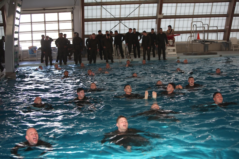 """Marines with Marine Wing Communications Squadron 28 swim across the combat pool at Marine Corps Air Station Cherry Point, N.C., Feb. 17, 2016. More than 85 noncommissioned officers with the squadron participated in the physical training exercise """"Chaos,"""" which tested their warfighting abilities: strength, communication and dependability. During the training the Marines were put into fire teams where they had to navigate the obstacle course, trek through the combat pool and hike one-mile with a simulated casualty and assault load. The purpose of the event was to build on unit cohesion, esprit de corps and mental and physical resiliency."""