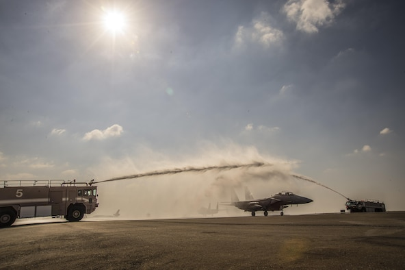 U.S. Air Force 380 Expeditionary Civil Engineer Squadron Fire Engines spray water over a taxing F-15E Strike Eagle at an undisclosed location in Southwest Asia, Feb. 13, 2016. The water arch was brought to the flight line to celebrate the achievement of the weapon systems officer on board who surpassed the 1,000 combat flight hour milestone during the mission. (U. S. Air Force photo by Tech. Sgt. Frank Miller/Released)