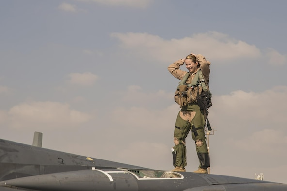 391st Expeditionary Fighter Squadron weapon systems officer, call sign Swat, stands on top of an F-15E Strike Eagle following a combat sortie at an undisclosed location in Southwest Asia, Feb. 13, 2016. Swat surpassed the 1,000 combat flight hour mark during the mission in support of Operation Inherent Resolve. (U. S. Air Force photo by Tech. Sgt. Frank Miller/Released)