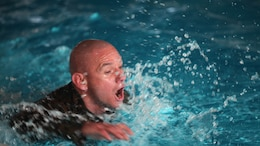 """Sergeant Maj. Rogelio Deleon swims in a combat pool at Marine Corps Air Station Cherry Point, N.C., Feb. 17, 2016. More than 85 noncommissioned officers with Marine Wing Communications Squadron 28 participated in the physical training exercise """"Chaos,"""" which tested their warfighting abilities: strength, communication and dependability. During the training the Marines were put into fire teams where they had to navigate the obstacle course, trek through the combat pool and hike one-mile with a simulated casualty and assault load. The purpose of the event was to build on unit cohesion, esprit de corps and mental and physical resiliency. Deleon is the sergeant major of MWCS-28."""