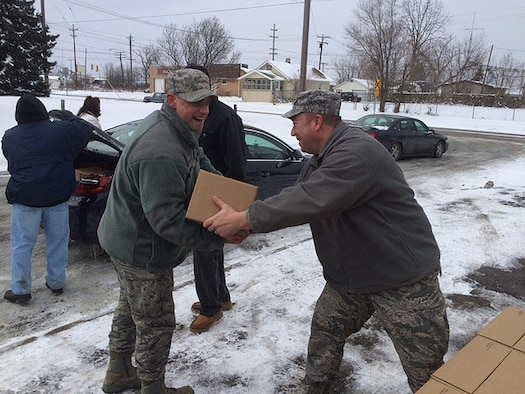 Staff Sgt. David Whitney (right) hands a box of bottled water to Staff Sgt. Parker Smith at Word Temple Church in Flint, Michigan, Feb. 10. Whitney and Parker are 339th Recruiting Squadron recruiters based in Flint. Due to massive amounts of lead found in Flint water, millions of bottles of water have been donated to the city and surrounding area since the crisis began. Residents are unable to drink or bathe in the water. The two recruiters have been assisting in the recovery every Wednesday by distributing water and filtration kits, and helping test for lead. (U.S. Air Force photo by Airman 1st Class Karl Fletcher)
