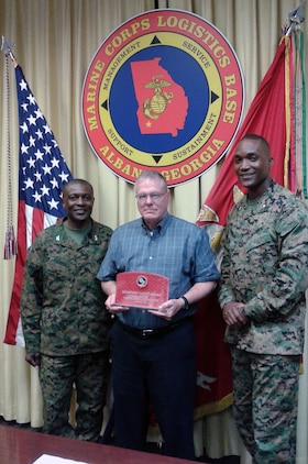 Col. James C. Carroll III (left), commanding officer, Marine Corps Logistics Base Albany, presents Bob James (center), director, Operations and Training Division, MCLB Albany, the Quarterly Safety Award, during the CO's Quarterly Safety Council Meeting, Feb. 3. Assisted by Lt. Col. Nathaniel Robinson (right), executive officer, MCLB Albany, James accepted the safety award on behalf of the Ops division's workforce.