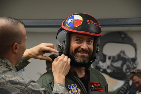 "NAVAL AIR STATION FORT WORTH JOINT RESERVE BASE, Texas – Hugh Jackman, ""Eddie the Eagle"" star, smiles here while Master Sgt. Jonathan Gibson, 301st Operations Support Flight non-commissioned officer in charge of aircraft section, adjusts his helmet Feb. 19 in preparation for flight. Jackman flew in an Air Force Reserve F-16 Fighting Falcon for more than 45 minutes above North Texas. (U.S. Air Force photo by Staff Sgt. Samantha Mathison)"
