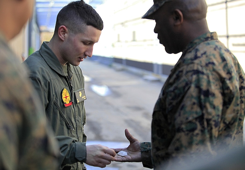 Manhattan, Kan.- native Lance Cpl. Gunnar I. Naughton, a team member with Identification Platoon, React Force Company, Chemical Biological Incident Response Force (CBIRF), receives a challenge coin from Sgt. Maj. Ronald L. Green, the 18th Sergeant Major of the Marine Corps, during Green's tour of Raymond M. Downey Responder Training Facility, Naval Annex Stump Head, Md., Feb. 18, 2016. Green visited the Marines, sailors and civilians with CBIRF at Naval Support Facility Indian Head and Raymond M. Downey Responder Training Facility. During Green's visit, he received a CBIRF brief given by the CBIRF Commanding Officer, Col. Stephen E. Redifer, viewed a static display of an Initial Response Force set-up, talked to CBIRF personnel, toured the Downey Responder Training Facility and had lunch with CBIRF staff noncommissioned officers.  When directed, CBIRF forward-deploys and/or responds with minimal warning to a chemical, biological, radiological, nuclear or high-yield explosive (CBRNE) threat or event in order to assist local, state, or federal agencies and the geographic combatant commanders in the conduct of CBRNE response or consequence management operations, providing capabilities for command and control; agent detection and identification; search, rescue, and decontamination; and emergency medical care for contaminated personnel. (Official USMC Photo by Sgt. Santiago G. Colon Jr./RELEASED)