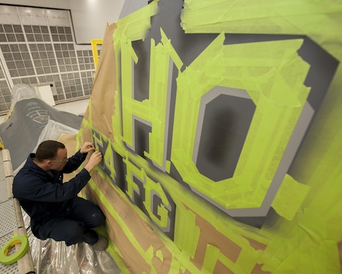 Senior Airman Paul Gatlin, an aircraft structural maintenance technician with the 49th Maintenance Squadron, finishes taping off the vertical stabilizer of the 54th Fighter Squadron's F-16 Fighting Falcon flagship at Holloman Air Force Base, N.M., Nov. 10, 2015. Corrosion control specialists have the unique task of ensuring every aircraft on base is able to withstand deterioration caused by the weather. (U.S. Air Force photo/Airman 1st Class Randahl J. Jenson)