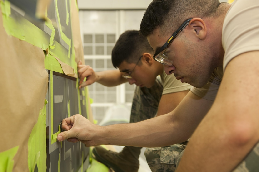 """Airmen 1st Class Robert Rocha (left) and Ryan Magusiak, aircraft structural maintenance technicians with the 49th Maintenance Squadron, tape off the tail of the 54th Fighter Squadron's F-16 Fighting Falcon flagship in preparation for painting at Holloman Air Force Base, N.M., Nov. 10, 2015. Corrosion control specialists stripped, primed and painted every flagship tail, replacing the Luke AFB symbol """"LF"""" with Holloman's symbol """"HO."""" (U.S. Air Force photo/Airman 1st Class Randahl J. Jenson)"""
