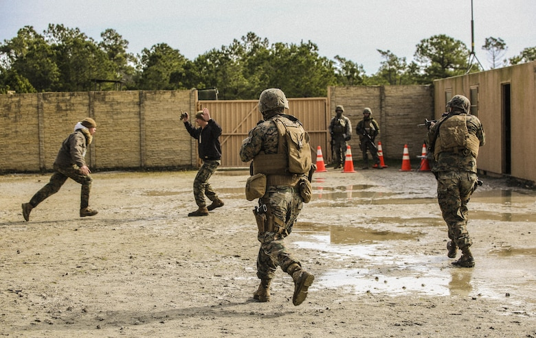 Marines with Bravo Company, 2nd Law Enforcement Battalion, simulate civilians in physical altercations at a forward observation base, which requires Marines to step in and take control of the situation during an interior guard training exercise at Forward Observation Base Hawk at Camp Lejeune, N.C., Feb. 17, 2016. The training prepared Marines to conduct real-life site security operations. (U.S. Marine Corps photo by Lance Cpl. Erick Galera/Released)