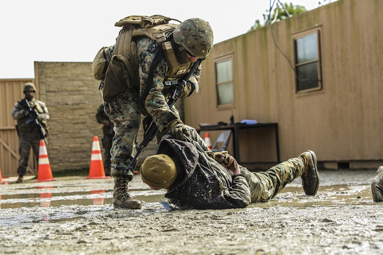 Marines with Bravo Company, 2nd Law Enforcement Battalion, subdue role players after a notional altercations at a forward observation base during an interior guard training exercise at Forward Observation Base Hawk at Camp Lejeune, N.C., Feb. 17, 2016. The training prepared Marines to conduct real-life site security operations. (U.S. Marine Corps photo by Lance Cpl. Erick Galera/Released)
