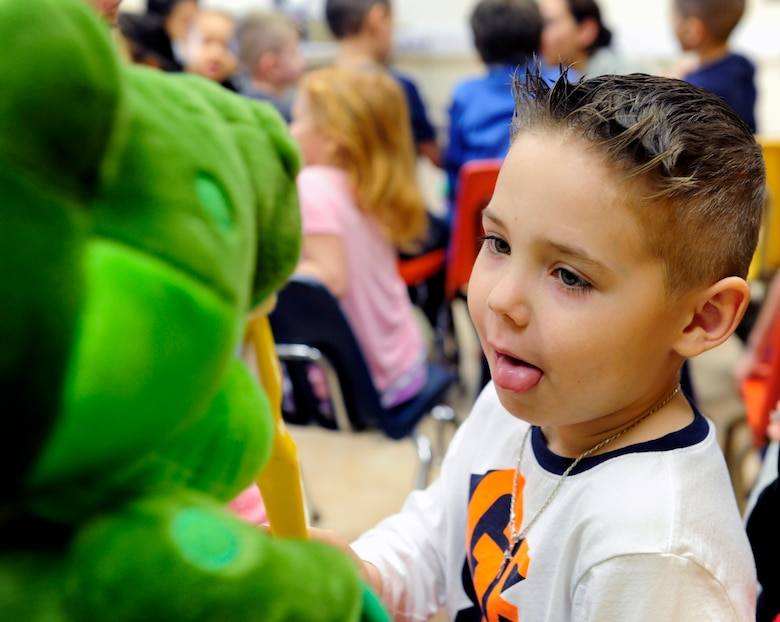 A child at Incirlik Unit School demonstrates proper toothbrush technique on a dinosaur puppet Feb. 19, 2016, at Incirlik Air Base, Turkey. Members of the 39th Medical Operations Squadron dental flight visited with elementary school children to discuss the importance of oral hygiene. (U.S. Air Force photo by Staff Sgt. Jack Sanders)