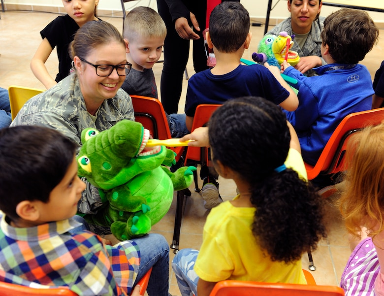 U.S. Air Force Master Sgt. Emily Jones, 39th Medical Operations Squadron dental flight chief, holds a puppet as children from the Incirlik Unit School demonstrate proper toothbrush technique Feb. 19, 2016, at Incirlik Air Base, Turkey. Proper technique ensure the toothbrush reaches the gums and tooth at an angle to best remove the most debris. (U.S. Air Force photo by Staff Sgt. Jack Sanders)