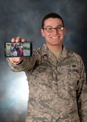 Airman 1st Class Ignacio Luna Jr., 28th Aircraft Maintenance Squadron weapons load crew member, proudly displays a photo of his family at Ellsworth Air Force Base, S.D., Feb. 10, 2016. Luna uses his family to motivate him to work hard and be the best Airman he can be. (U.S. Air Force photo by Airman Sadie Colbert/Released)