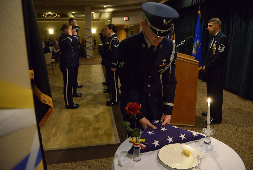 Members of the Cannon honor guard set a table honoring Americas who are still missing in action during the annual awards banquet Feb. 19, 2016, at Cannon Air Force Base, N.M. This table is ceremoniously set to show that Americans shall never forget the brave men and women who answered our nation's call and served the cause of freedom. (U.S. Air Force photo/Staff Sgt. Alexx Pons)