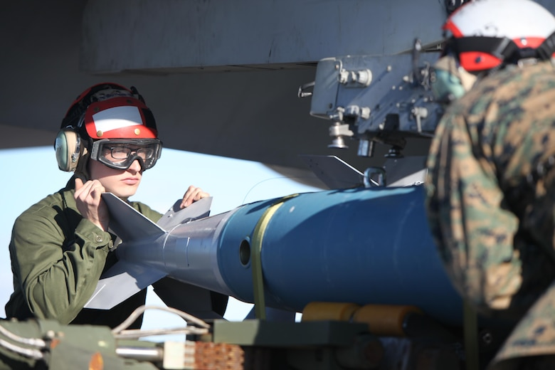 Lance Cpl. Stephen Tryen assists in lifting a BDU-45 practice bomb onto an F/A-18 Hornet during Exercise Coastal Predator at Marine Corps Air Station Cherry Point, N.C., Feb. 16, 2016. The practice bomb falls according to the trajectory of the aircraft while in flight and is used for training purposes. Coastal Predator is an exercise that included Marine Corps and Army aviation assets along with Air Force personnel and civilian contractors to conduct Forward Air Controller Airborne training in accordance with the pre-deployment training program. Tryen is an ordnance technician with Marine All Weather Fighter Attack Squadron 533. (U.S. Marine Corps photo by Cpl. Jason Jimenez/Released)