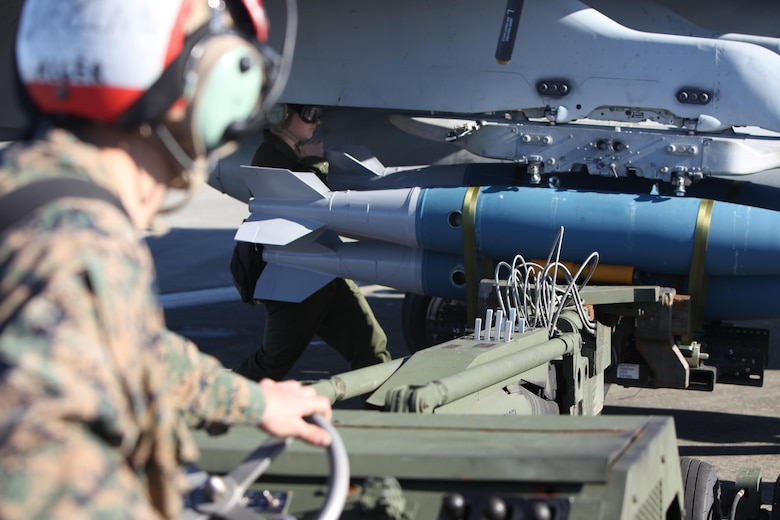 Marines operating an A/S 32K-1A/1B/1C SATS Weapon Loader load BDU-45 practice bombs onto an F/A-18 Hornet during Exercise Coastal Predator at Marine Corps Air Station Cherry Point, N.C., Feb. 16, 2016. The practice bombs fall according to the trajectory of the aircraft while in flight and is used for training purposes. Coastal Predator is an exercise that includes Marine Corps and Army aviation assets along with Air Force personnel and civilian contractors to conduct Forward Air Controller Airborne training in accordance with the pre-deployment training program.  (U.S. Marine Corps photo by Cpl. Jason Jimenez/Released)