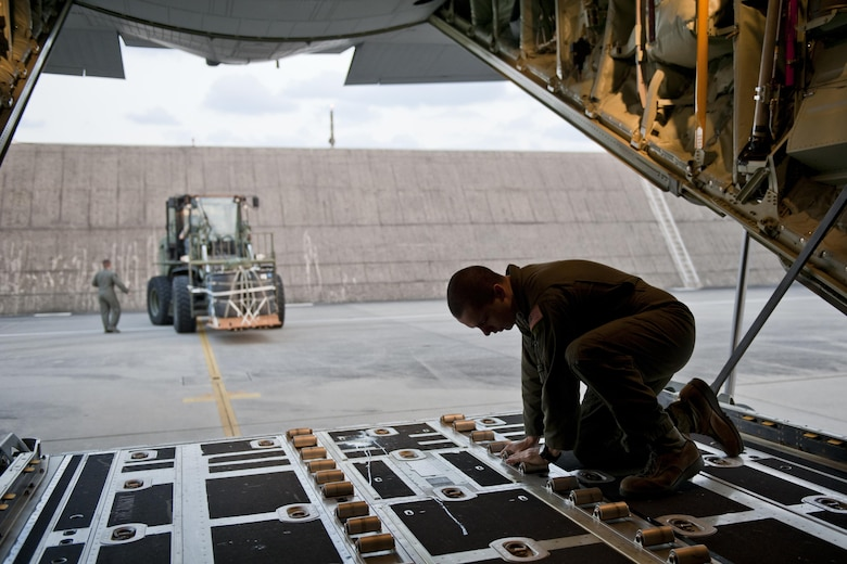 U.S. Air Force Senior Airman Zach Harmon, 17th Special Operations Squadron MC-130J Commando II loadmaster, prepares a cargo deck for loading during a training exercise Feb. 17, 2016, at Kadena Air Base, Japan. Harmon participated in a fast-reaction simulation that tested the squadron's capability to quickly and safely mobilize their entire fleet of aircraft for cargo drops, short runway landings and takeoffs, and helicopter air-to-air refueling. (U.S. Air Force photo by Senior Airman Peter Reft/Released)