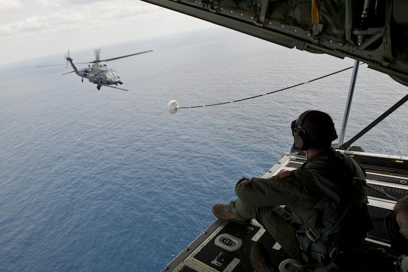 U.S. Air Force Senior Airman Zach Harmon, 17th Special Operations Squadron MC-130J Commando II loadmaster, observes a 33rd Rescue Squadron HH-60G Pave Hawk helicopter air-to-air refueling during a training exercise Feb. 17, 2016, off the coast of Okinawa, Japan. The 17th SOS simulated a quick-reaction, full-force sortie that tested the unit's mobilization of the entire MC-130J fleet. (U.S. Air Force photo by Senior Airman Peter Reft/Released)
